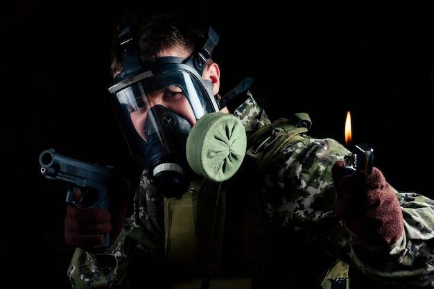 방독면을 쓴 남자는 검은 배경에 총과 라이터를 보관합니다. 마스크가 위협하는 가장 큰 문제입니다.