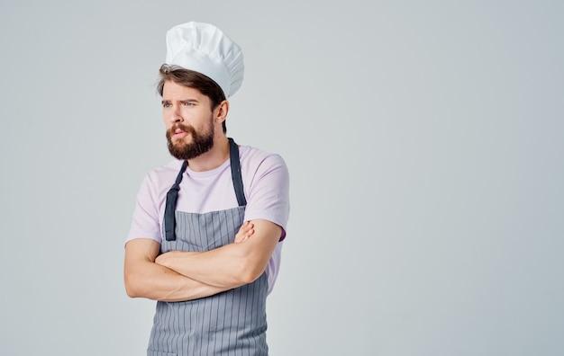 Мужчина в сером фартуке и головном уборе жестикулирует как профессиональный повар.