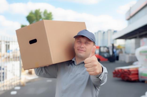 倉庫とローダーを背景に段ボール箱を手に灰色のスーツを着た男