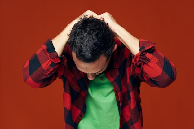녹색 티셔츠를 입은 남자와 빨간색 배경에 머리를 앞으로 기울이고 있는 격자 무늬 셔츠