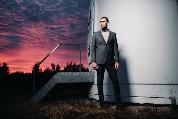 日没後、灰色のビジネススーツを着た男性が風車の隣に立っています。夜の風車の近くのビジネスマン。未来の現代的な概念。