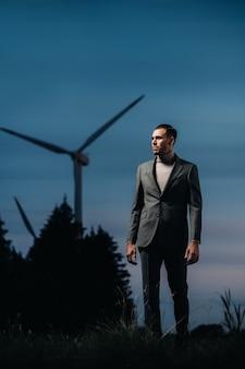 회색 비즈니스 정장을 입은 남자가 일몰 후 풍차 옆에 서 있습니다. 밤에 풍차 근처 사업가입니다. 미래의 현대적인 개념입니다.