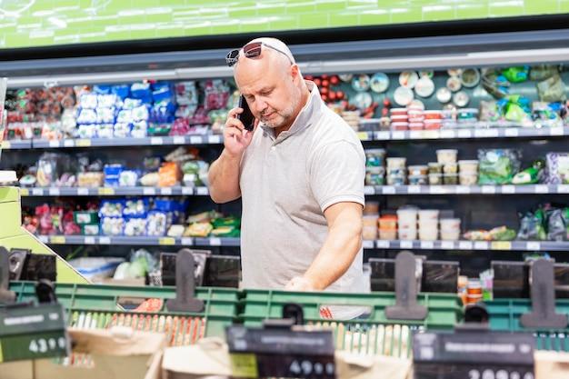 Мужчина в продуктовом магазине с телефоном
