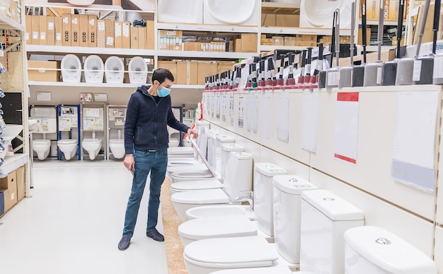 Мужчина в строительном магазине выбирает унитаз