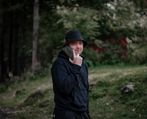 帽子と黒いパーカーを着た男が電話で話し、森の背景に対してカメラを見ます