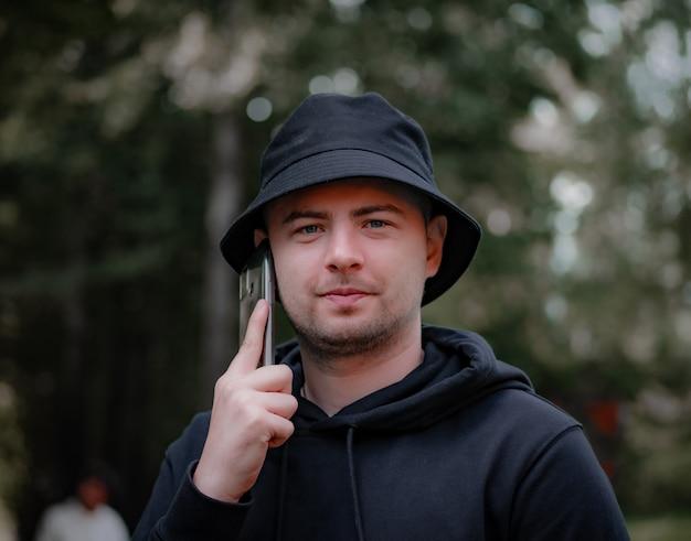 帽子と黒いパーカーを着た男が電話で話し、カメラを見る