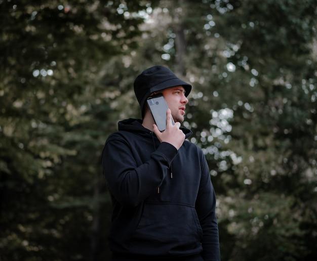 帽子と黒いパーカーを着た男が電話で話し、森を背景に横を向いています