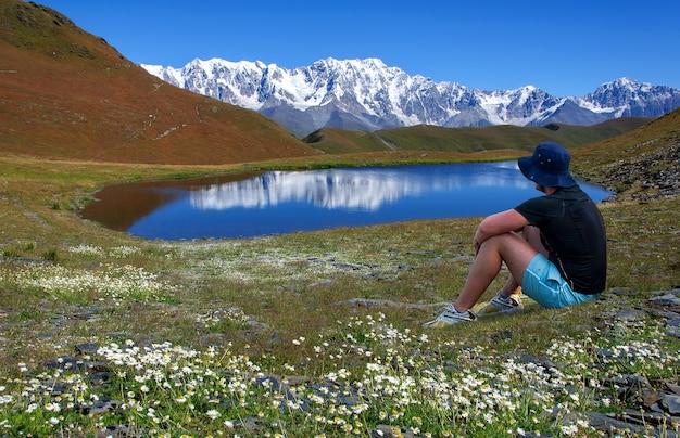 帽子をかぶった男がジョージアスヴァネティの雪をかぶった山々を見下ろす湖の近くの花の牧草地で休んでいます
