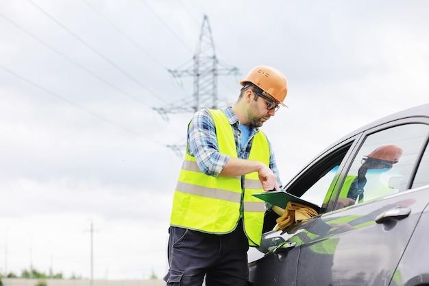 Мужчина в каске и форме, электрик в поле. профессиональный инженер-электрик проверяет линии электропередач во время работы.