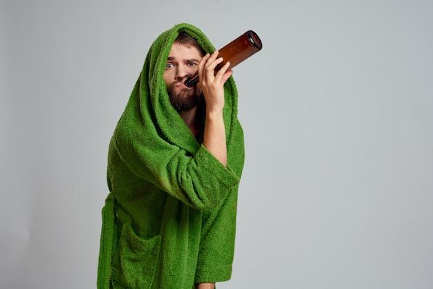朝の家で上着を着た男が自宅でビールアルコールのボトルを持って退屈、失業者