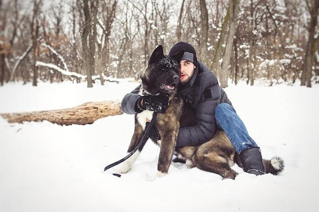 재킷과 니트 모자를 입은 남자가 미국 아키타 개와 함께 눈 덮인 숲을 산책