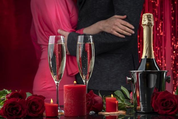 Мужчина в куртке и женщина в розовом платье танцуют, обнимая свечи и роскошные розы.
