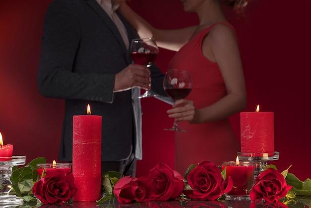 Мужчина в куртке и женщина в розовом платье держат очки, танцуют, обнимаются