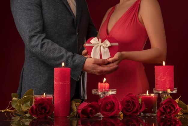 Мужчина в куртке и женщина в красном платье держат в форме подарочные коробки.