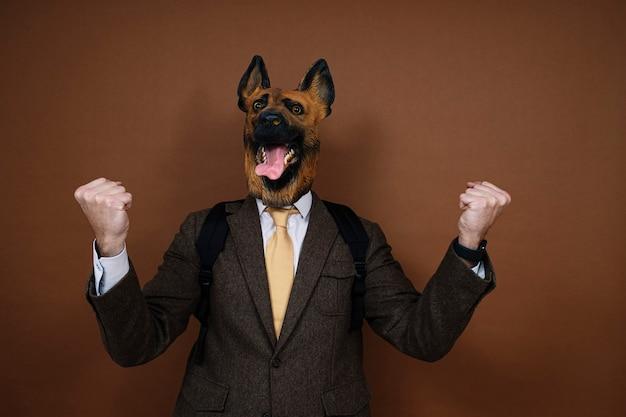 라텍스 개 머리 마스크에 남자가 손을 위로 상승