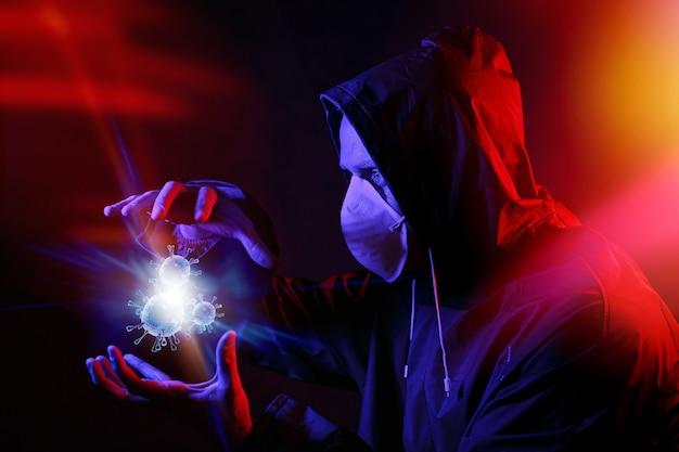 赤と青の光の中でマスクと化学防護服を着た男。ウイルスと戦う
