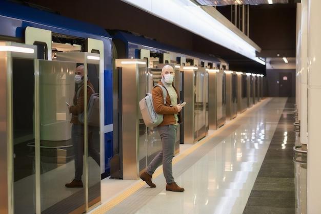코로나 바이러스 확산을 막기 위해 의료용 마스크를 쓴 남자가 현대 지하철 차량을 떠나는 동안 핸드폰을 들고있다