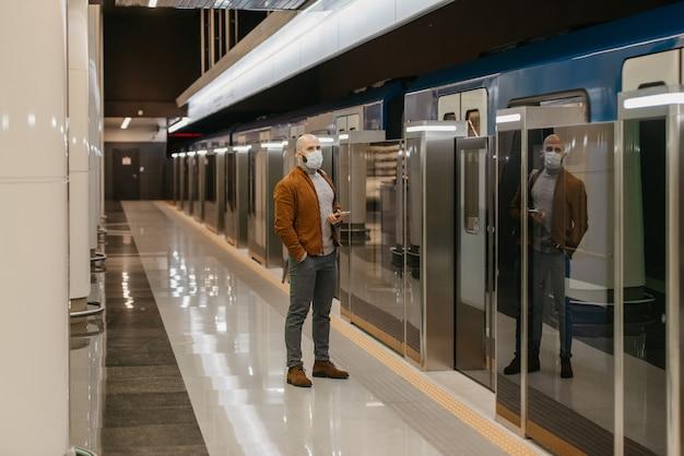 コロナウイルスの蔓延を防ぐために医療用フェイスマスクを着用した男性が、地下鉄で電車を待っている間、携帯電話を持っています。サージカルマスクをかぶったハゲ男が社会的距離を保っています。