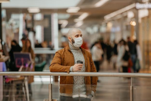 コロナウイルスの蔓延を防ぐために医療用フェイスマスクを着用した男性が、ショッピングセンターで待っている間コーヒーを持っています。サージカルマスクのハゲ男が社会的距離を保っています。