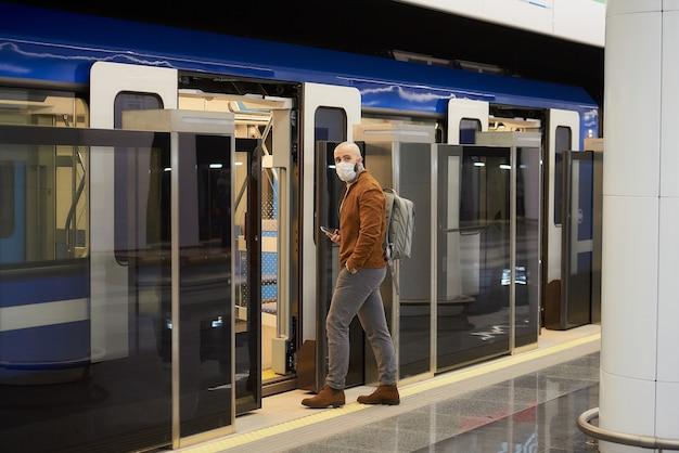 신종 코로나 바이러스 감염증 확산을 막기 위해 의료용 마스크를 쓴 남자가 현대 지하철에 탑승하면서 스마트 폰을 들고있다