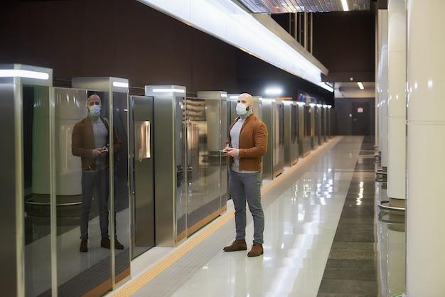 코로나 바이러스 확산을 막기 위해 의료용 마스크를 쓴 남자가 지하철에서 기차를 기다리는 동안 스마트 폰을 들고있다