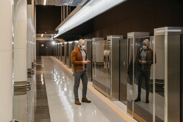 コロナウイルスの蔓延を防ぐために医療用フェイスマスクを着用している男性が、地下鉄で電車を待っている間、スマートフォンでニュースをスクロールしています。サージカルマスクをかぶったハゲ男が社会的距離を保っています。