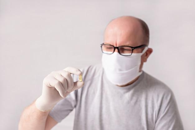 Мужчина в медицинской маске и перчатках с планшетом в руках.