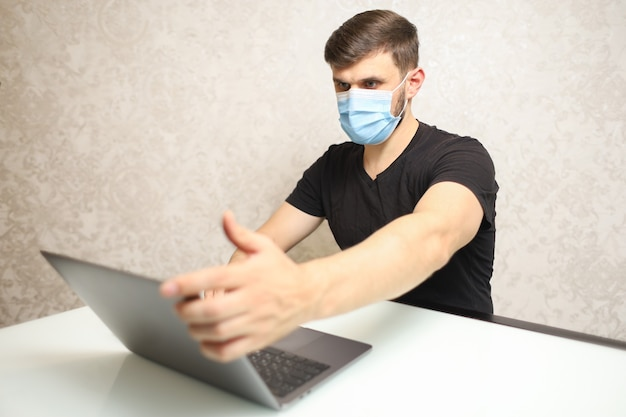 자기 격리에 의료 마스크를 쓴 남자가 노트북에서 일한다