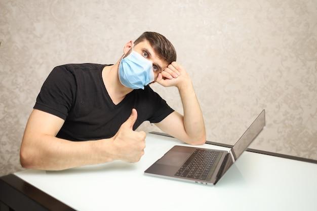 自己隔離の医療マスクの男はラップトップで動作します