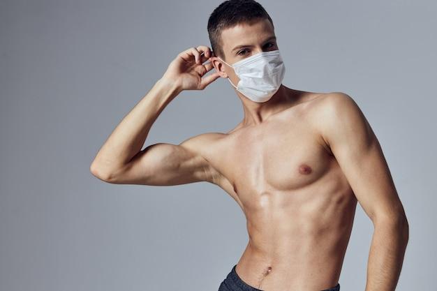 펌핑 프레스가 달린 의료용 마스크를 쓴 한 남자가 머리 근처에서 손을 잡고 건강을 보호합니다.