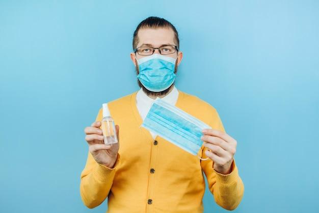 手に消毒剤を入れた医療用マスクを着た男性。感情的な男が消毒器の使用方法を示しています。コロナウイルスの流行における消毒剤の使用。 covid 2019