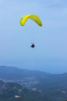 パラシュートで男が山の上を飛んでいます。