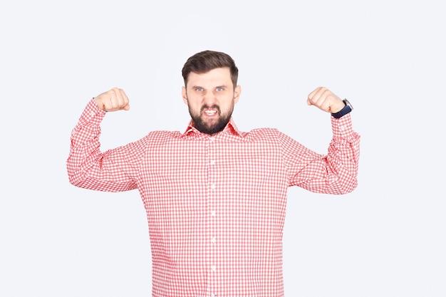 분홍색 체크 무늬 셔츠를 입은 남자가 팔뚝을 과시합니다. 턱수염을 가진 남자가 위협적인 포즈를 취합니다.
