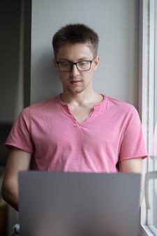 ピンクのシャツと眼鏡をかけた男性が窓の近くに座ってノートパソコンで作業しています