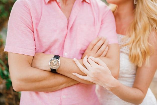 Мужчина в розовой рубашке скрестил руки на груди, блондинка нежно обнимает его за локоть.