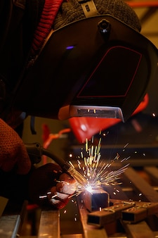Мужчина в защитной маске проводит сварочные работы в гараже.