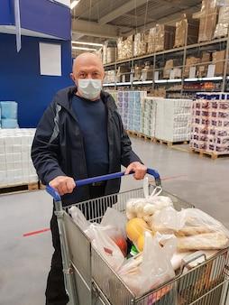 코로나 바이러스가 유행하는 동안 보호 마스크를 쓴 남자가 슈퍼마켓에서 제품과 함께 쇼핑 카트를 가져갑니다.