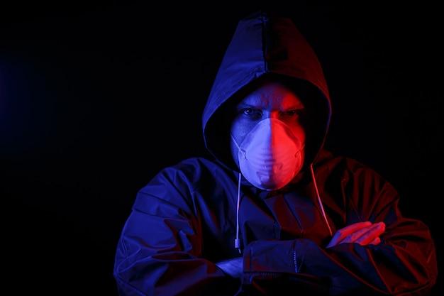 보호용 고무복과 흰색 의료용 마스크를 쓴 남자. 바이러스 보호. 빨간색과 파란색으로 조명됩니다.
