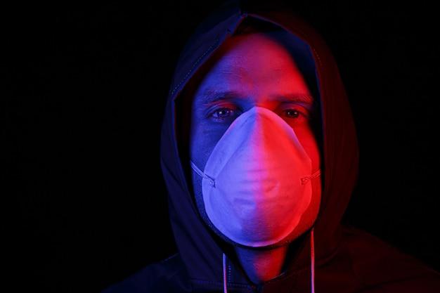 保護ゴムのスーツと白い医療用マスクを身に着けた男性。ウイルス防護。赤と青で照らされています。
