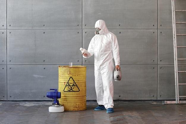 防護服とマスクを着た男性が黄色い樽の横にあるボトルを調べます