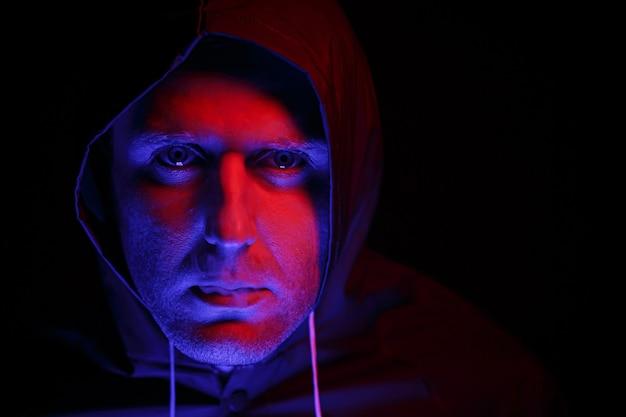 방호복을 입은 남자가 연기를 내뿜고 있다. 할로윈 이미지 개념입니다. 바이러스 보호. 컬러 조명으로 조명