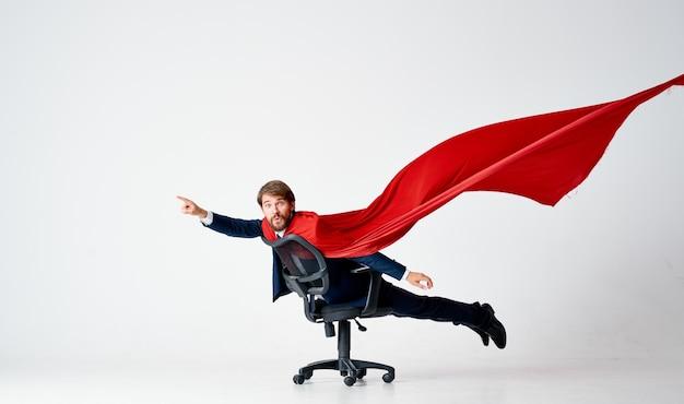 赤いマントのスーツを着た男が椅子のスーパーヒーローに乗る