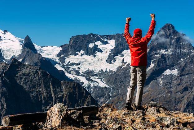 山の頂上に赤いジャケットを着た男、背面図。観光客は山の頂上に立って、起こっていることを楽しんでいます。アクティブなスポーツのコンセプト。男は山の頂上に着いた。コピースペース