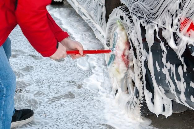 赤いジャケットを着た男性が、泡を注いだ黒い車のホイールをセルフサービスの洗車機でブラシでこすります