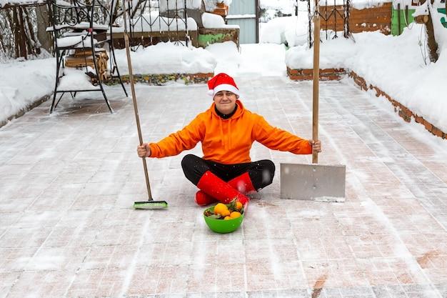 Мужчина в красной новогодней шапке сидит на территории двора с кистью, лопатой и тарелкой с мандаринами.