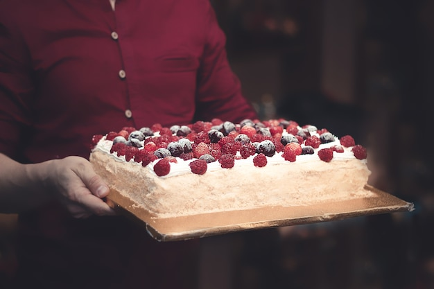 赤いシャツを着た男性が、カフェの暗い背景にベリーのパイを手に持っています。