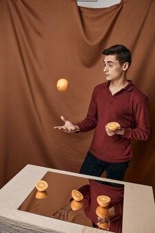 赤いシャツのエレガントなスタイルの男と鏡付きのテーブルの手にオレンジ。