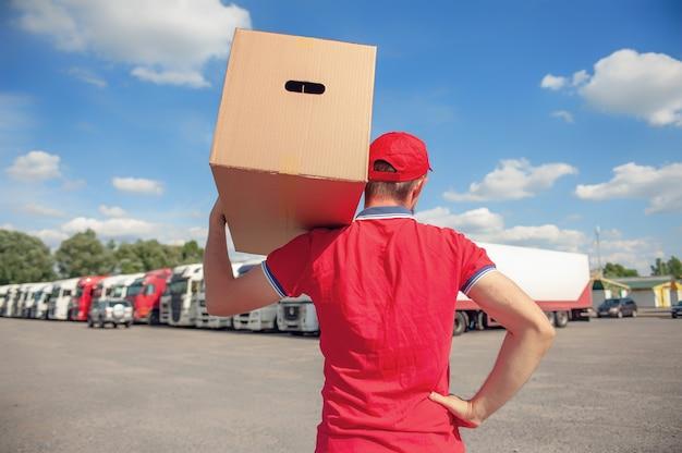 バンのスペースに対して段ボール箱を手に赤いスーツを着た男