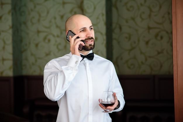 Мужчина в ресторане разговаривает по телефону.