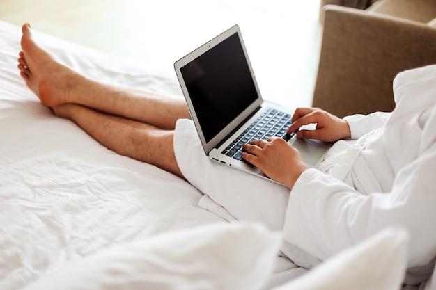 ローブを着た男性が、コンピューターを足元に置いてベッドに横になっています。フリーランス、在宅勤務。顔なし。ホテルの男性、コンピューターの寝室で働いています。垂直